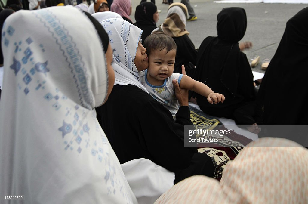 A baby is held by a woman during prayers in the Muslim community of Maharlika Village on March 6, 2013 in Taguig, Philippines. The peace rally was held to call for an end to hostilities in the ongoing crisis in Sabah. Fighting has broken out anew in the village of Lahad Datu, Sabah, Malaysia as Malaysian security forces comb the coastal areas where the 'Royal Sultanate Army of Sulu' was thought to have been hiding. Around 200 armed followers of self-proclaimed Sultan of Sulu Jamalul Kiram III in the restive southern provinces of Sulu and Tawi-Tawi in Mindanao crossed over to neighboring Sabah last February 12 to lay claim to territory as ancestral land, triggering clashes with Malaysian security forces. Philippine diplomatic officials confirmed yesterday that security forces in Malaysia have conducted airstrikes and ground assault on the 'royal army' of the Sultanate of Sulu in Lahad Datu, Sabah. A total of 17 followers of self-proclaimed Sultan of Sulu Jamalul Kiram III and eight Malaysian security forces were killed in the villages of Lahad Datu and Semporna in Sabah.