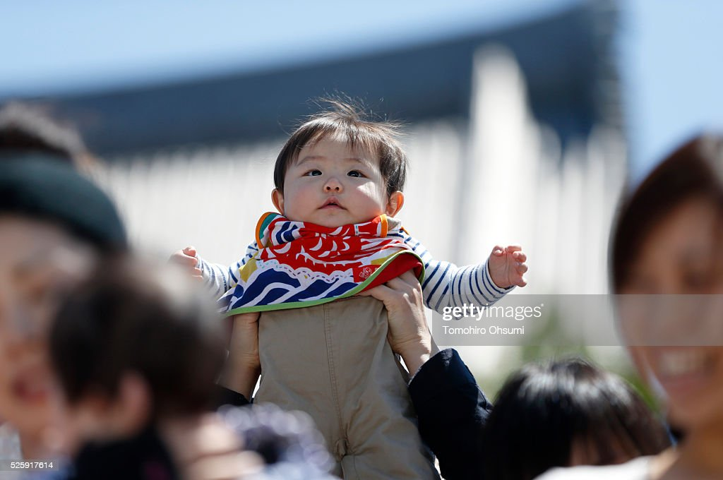 A baby is held by his fater during the opening ceremony of the Nakizumo or crying baby sumo contest at Sensoji Temple on April 29, 2016 in Tokyo, Japan. Babies compete crying at this traditional festival which is believed to bring growth and good health to the infants.
