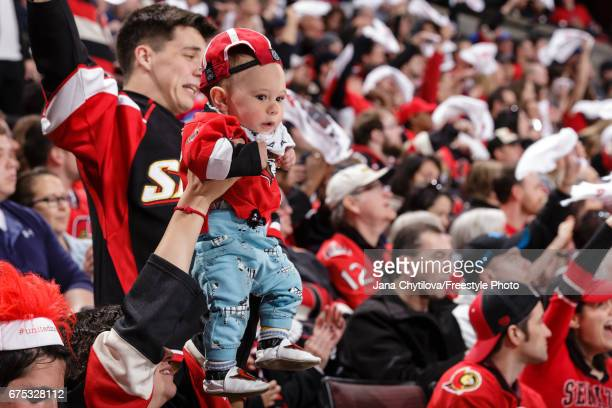A baby is held up as fans wave towels during a game between the Ottawa Senators and the New York Rangers in Game Two of the Eastern Conference Second...