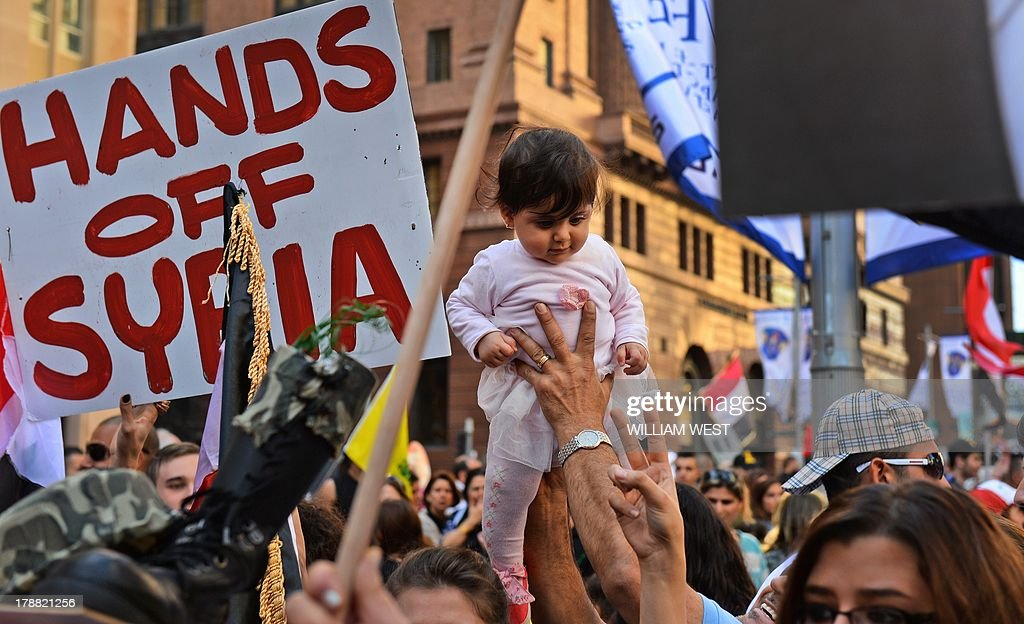 A baby is held up in front of a placard during a protest against a possible US military strike against Syria, in Sydney on August 31, 2013. Carrying placards reading 'Hands off Syria' and bearing the face of Syrian President Bashar al-Assad, protesters gathered in Sydney's Martin Place to voice their concerns about a US military assault. AFP PHOTO/William WEST