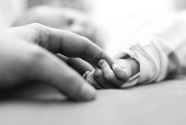 right after birth, baby is holding father's finger