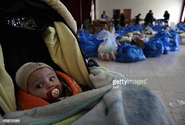 A baby is seen in a pram in front of bags containing food items for the poor at a food bank in Nicosia the capital of the east Mediterranean island...