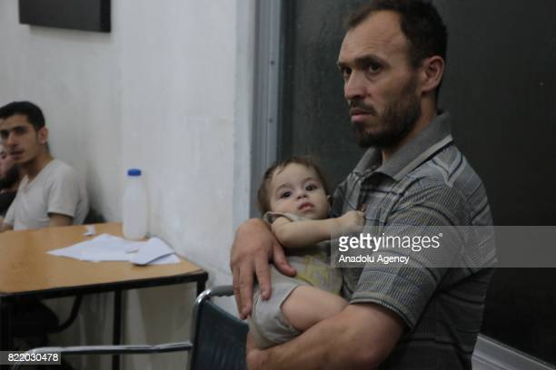 A baby is seen in his father's arms as they wait to receive treatment at a sahra hospital after Assad Regime's forces carried out airstrike over the...