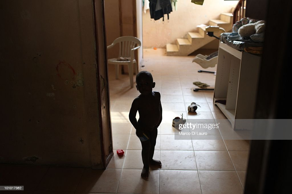 A baby is seen in the basement where he sleeps at the Faith Hope Love Infant Rescue Orphanage managed by a US citizen named Dorothy Pearce on February 4, 2010 in Port Au Prince, Haiti. Dorothy Pearce a US Citizen founded the Faith Hope Love Infant Rescue five years ago answering what she describes as a 'call by God' to leave her job as a real estate agent in Miami to come to Haiti. She runs the organization from her home in Port-au-Prince taking in children whose families are unable to support them. She is currently caring for 20 children. In the backyard strewn with rubbish, ten babies lie sleeping on the dirty concrete floor under a canopy of plastic sheeting, many are newborn. The older children play largely unobserved by the nannies barefoot amongst rusted tins and dirty nappies. A fetid swimming pool is covered with a cloud of mosquitoes. Three dogs, whose feces litter the small concrete play area, lick the children's faces as they play and lie on the floor. Several of the children are HIV positive and many suffer with severe disabilities. Most of the children appear listless, either clamouring to be held or curled up sleeping awkwardly on the floor. Others sit crying, unattended. One of the children, Alexandra, 2, was injured in the earthquake. Pearce who has not received any medical training, cuts dead flesh from an open wound on the injured child's foot as she screams in agony. Pearce has not registered her charity with the Haitian government and the orphanage is entirely unregulated. Prior to the earthquake that devastated the island on January 12th, there were an estimated 380,000 children living in orphanages in Haiti, 500 of which were unregistered. Since the disaster, in which thousands of children were separated from their families, the dangers facing Haiti's orphans have never been more acute.