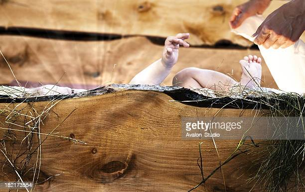 Baby Jesus lying in wooden crib.