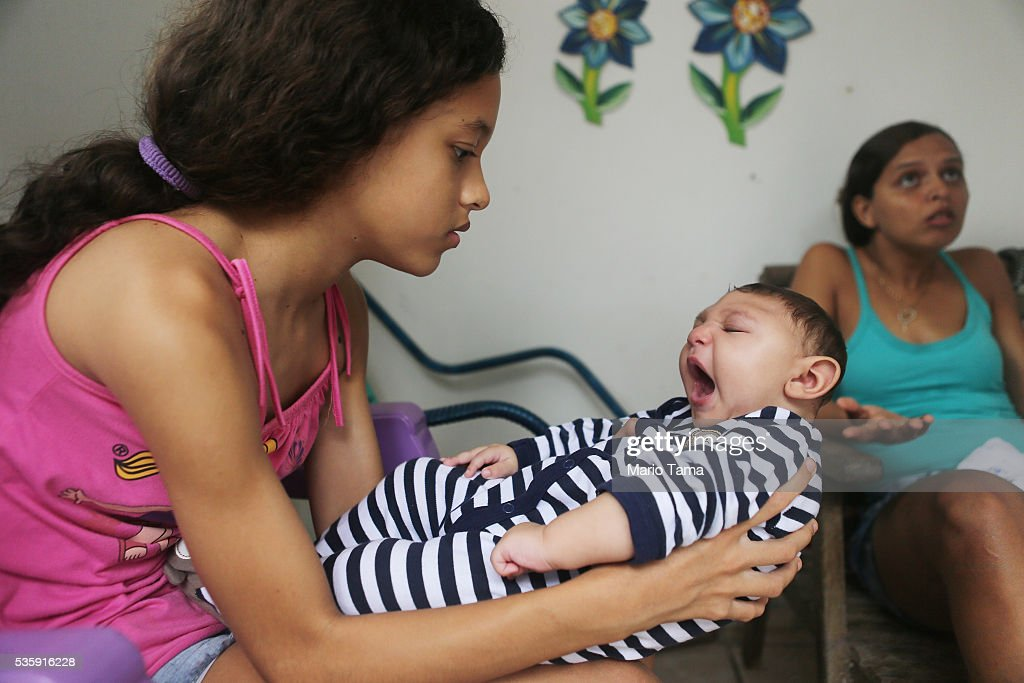 Baby Juan Pedro, who has microcephaly, is held by his sister Jennifer Karine as mother Daniele Santos sits (R) on May 30, 2016 in Recife, Brazil. Microcephaly is a birth defect linked to the Zika virus where infants are born with abnormally small heads. The city of Recife and surrounding Pernambuco state remain the epicenter of the Zika virus outbreak, which has now spread to many countries in the Americas. A group of health experts recently called for the Rio 2016 Olympic Games to be postponed or cancelled due to the Zika threat but the WHO (World Health Organization) rejected the proposal. The Olympic torch passes through Recife May 31.