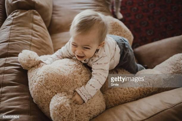Baby jumping on teddy bear