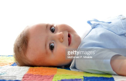 Baby laying down on colorful blanket : Stock Photo
