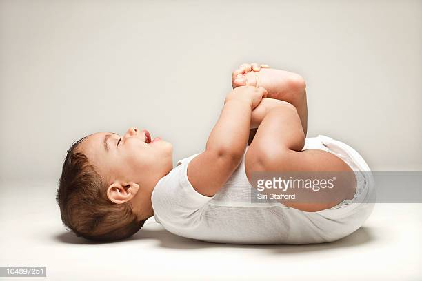 Baby laying on back holding feet smiling