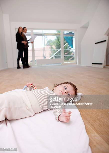 Baby laying on blanket in empty room