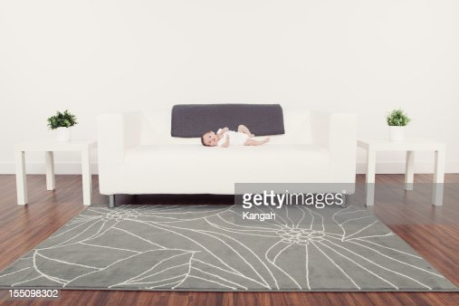 Baby laying on couch : Stock Photo