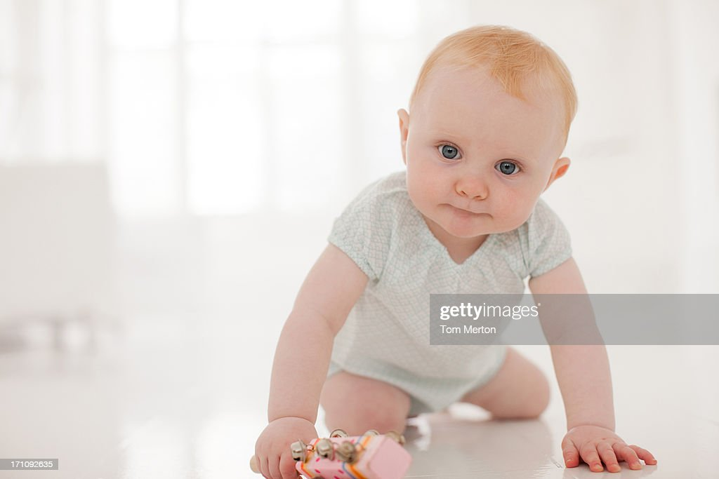 Baby leaning on floor : Stock Photo