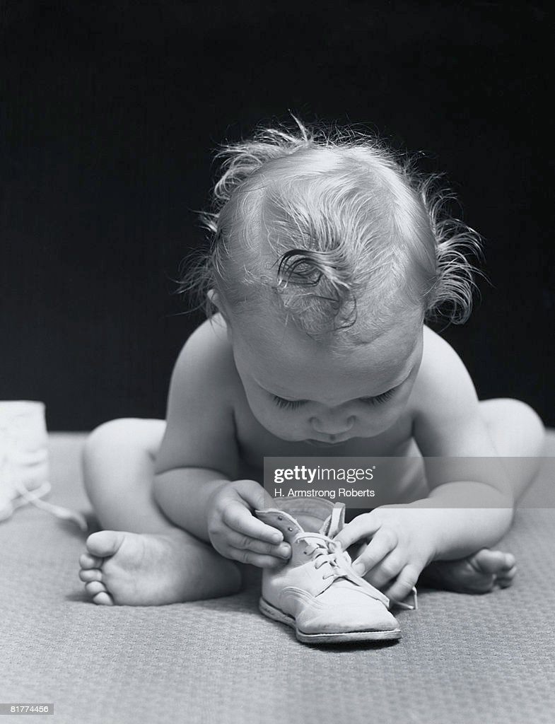 Baby leaning over playing with shoe. : Stock Photo
