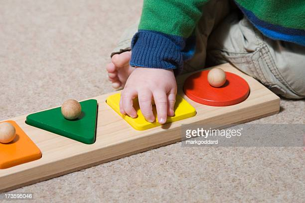 Baby learning to play using large wooden puzzle pieces
