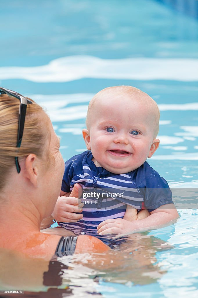 Baby learning to swim with his mother : Stock Photo