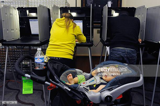 A baby lies in a stroller as his mother casts her ballot for the US presidential election at the BlairCaldwell African American Research Library in...