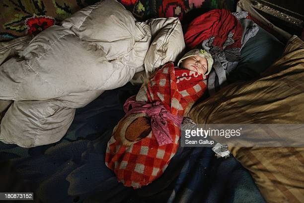 A baby lies swaddled in a oneroom home in the abjectly poor Roma settlement of Ponorata on September 10 2013 in Ponorata Romania Marinela and her...