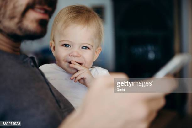 Baby looking at camera while father reads phone
