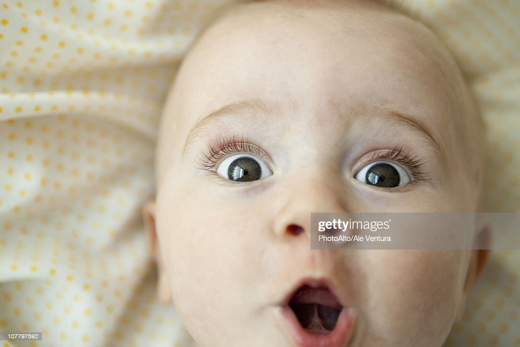 Baby looking at camera with surprised expression, portrait : Stock Photo