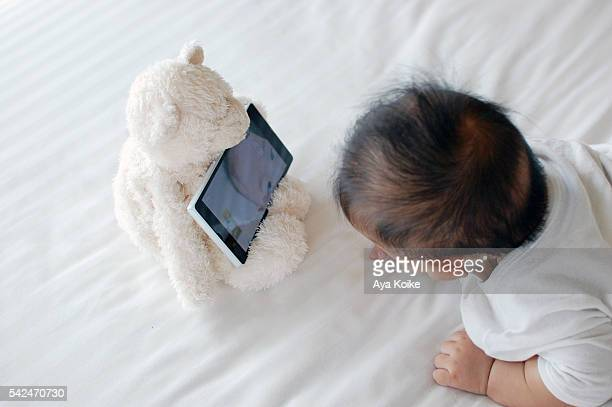 A baby looking at own face displayed on teddy bear's smartphone