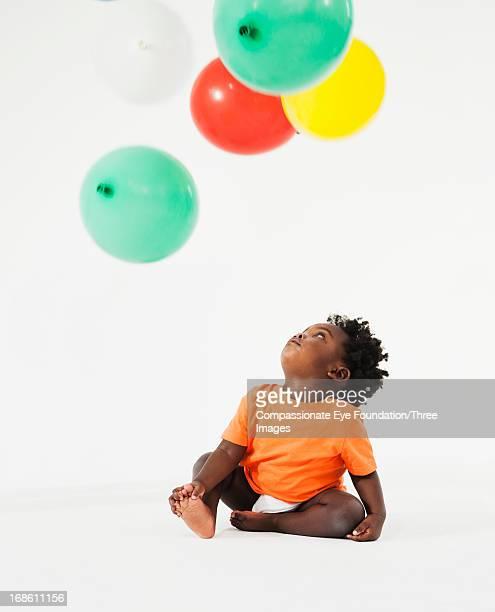 Baby looking up at balloons