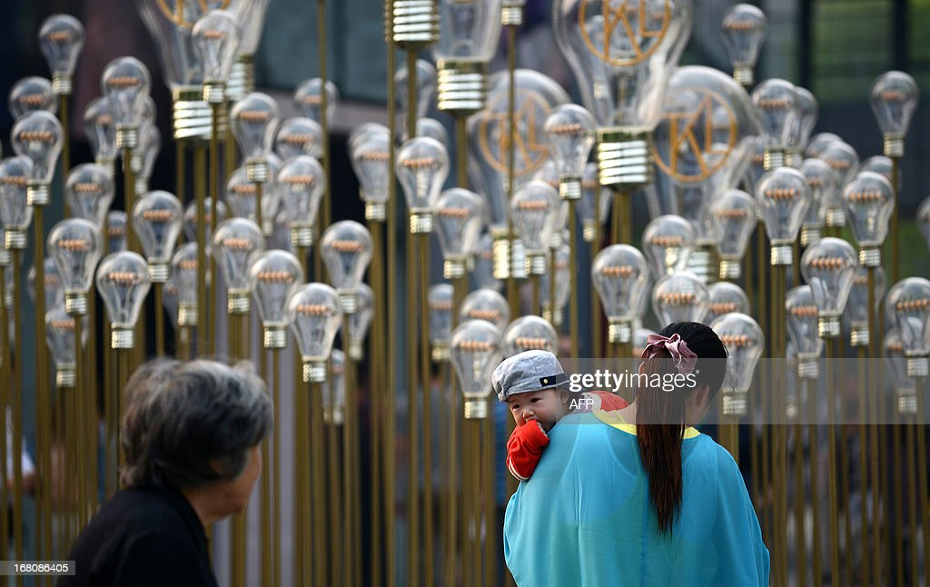 A baby (C) looks at an elderly woman walking in front of a group of bulbs at a shopping mall in Beijing on May 5, 2013. Manufacturing activity in China slowed slightly in April from the previous month, official data showed on May 1, in a sign of further weakness in the world's second-biggest economy.