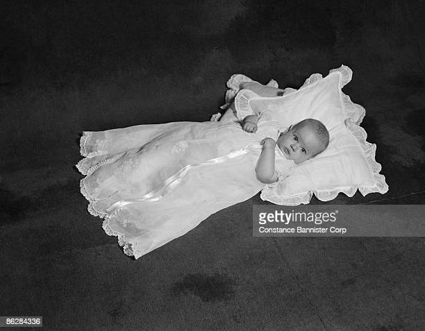 Baby lying down in christening gown