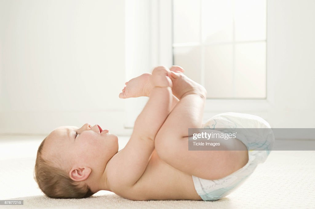A baby lying on its back : Stock Photo