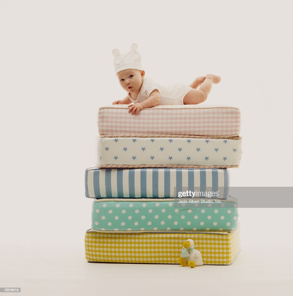Baby (3-6 months) lying on stack of mattresses