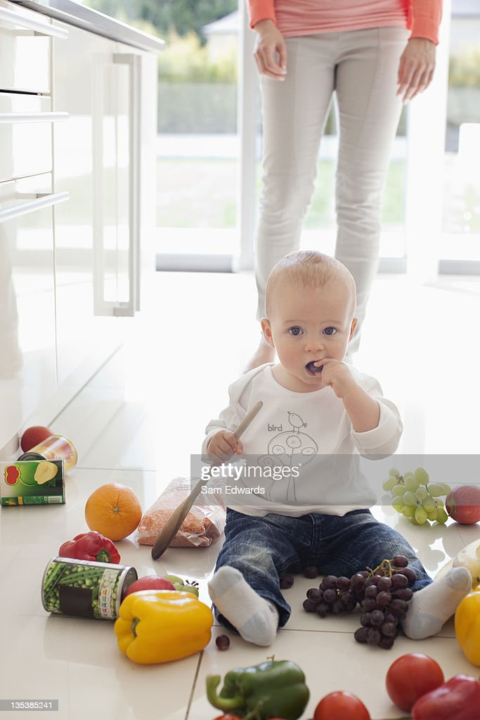 Baby making mess on floor with food : Stock Photo