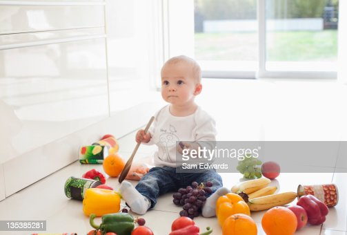 Baby making mess on floor with food : Stockfoto