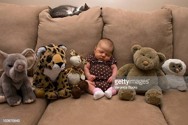 Baby on a couch surrounded by plush toys