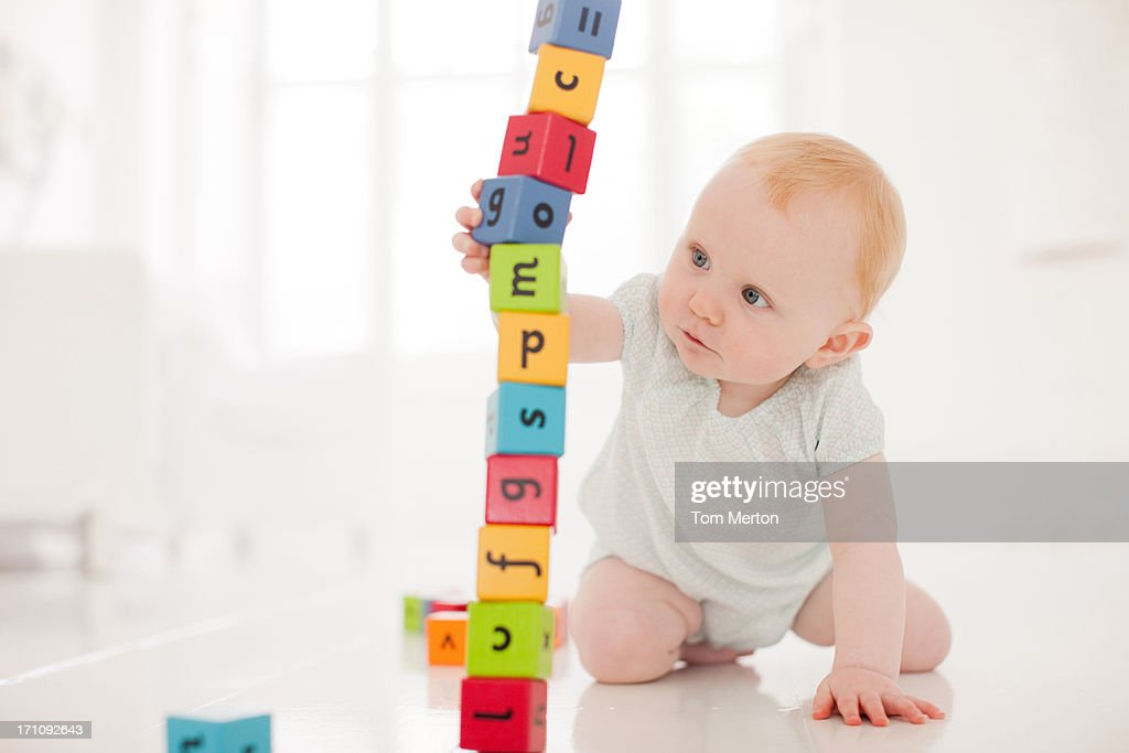 Baby on floor pulling wood block from middle of stack : Stock Photo