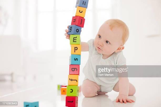 Bébé sur le sol avec tirant en bois pâté de maisons du cœur de la pile