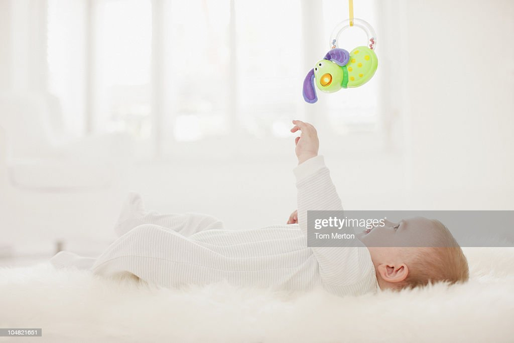 Baby on rug reaching for hanging toy overhead : Stock Photo