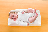 Cute newborn baby lying on a white baby scale