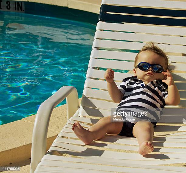 Baby on sun bed by pool with sunglasses