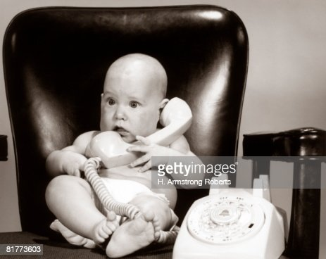 Baby on telephone, playing executive businessman. : Stock Photo
