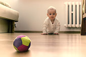 Baby on the floor is going to crawl towards the ball.