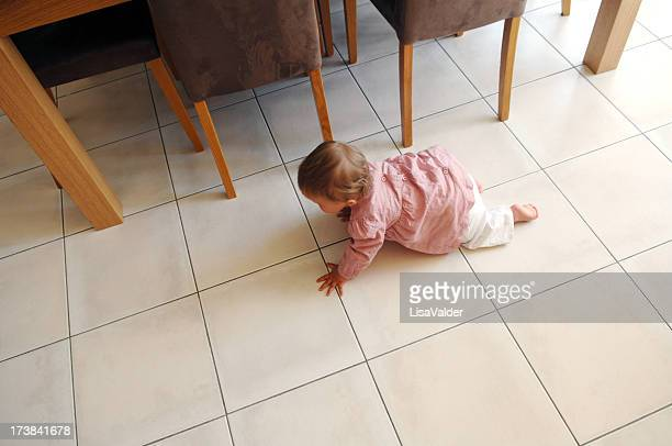 A baby on the move in the kitchen floor