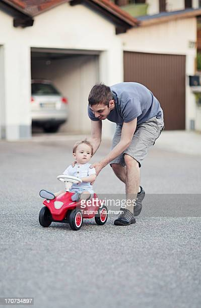 Baby on toy car being pushed by daddy