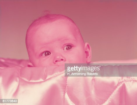 Baby peeking over top of pink silk quilted blanket. (Photo by H. Armstrong Roberts/Retrofile/Getty Images) : Stock Photo