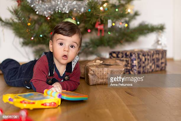 Baby playing in front of Christmas tree