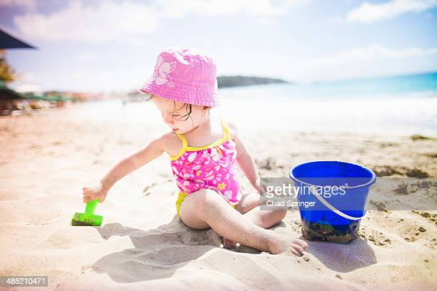 Baby playing on sandy beach with bucket and spade