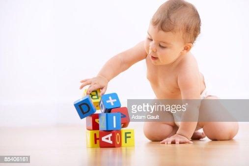 Baby playing with alphabet blocks : Stock Photo
