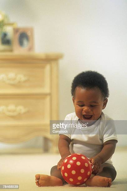 Baby playing with ball on floor