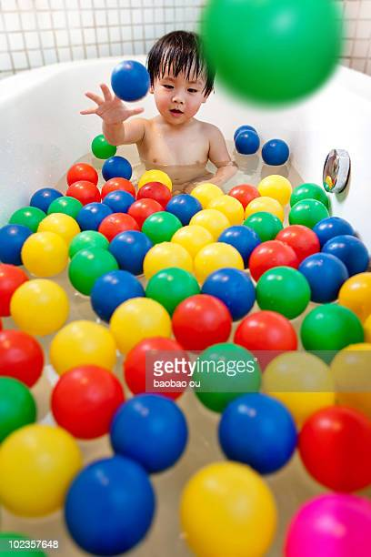 Baby playing with color balls in the bathtub