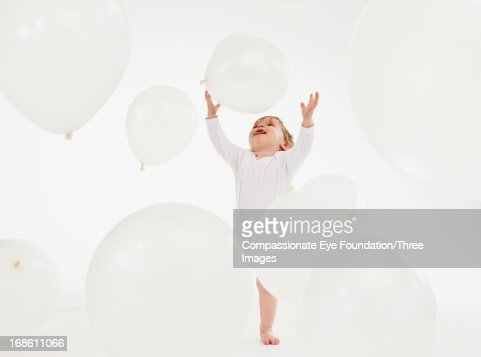 Baby playing with large balloons