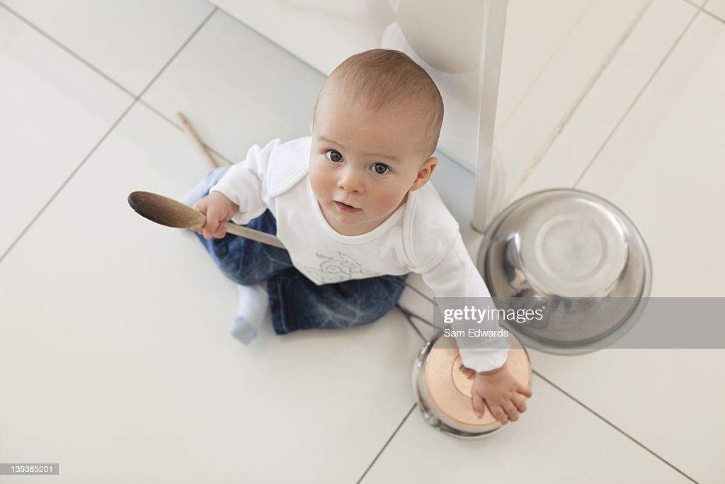 Baby playing with spoon and bowls : Stock Photo