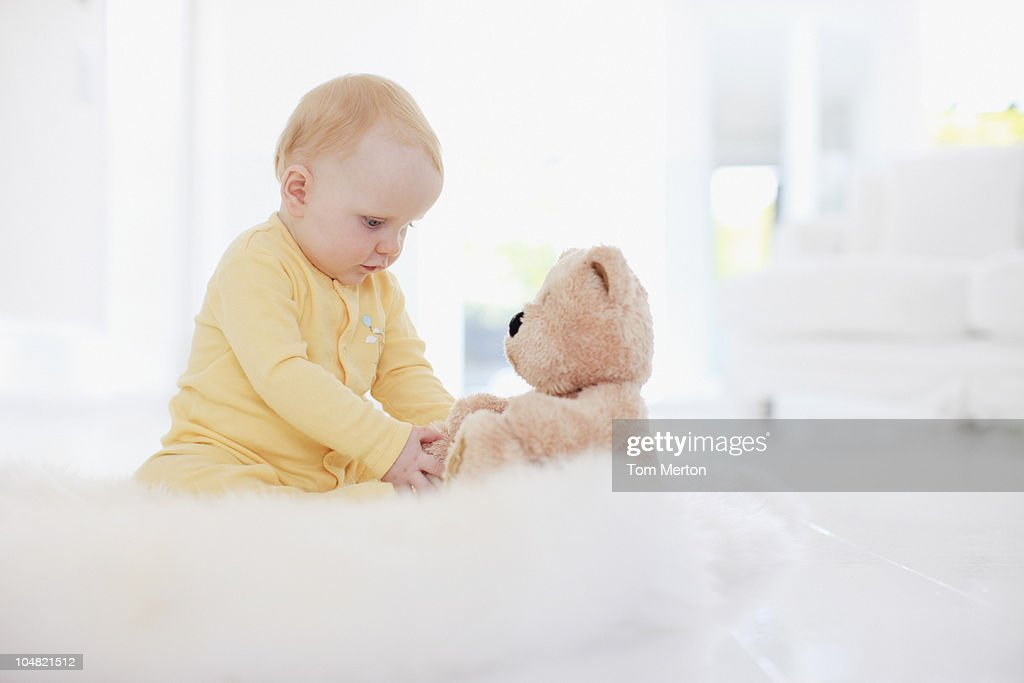 Baby playing with teddy bear on rug : Stock Photo